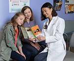 Woman and daughter with Dr. Yi Zeng looking at brochure on HPV