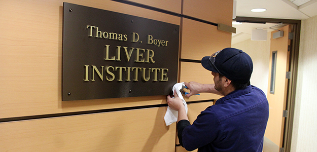 UA Facilities' Adam Jacobs tightens the final screw on new Liver Institute signage