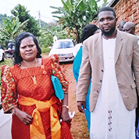 Dr. Bailey in Uganda doing an away rotation while a resident at the University of Arizona, visits the host family that he stayed with during his undergrad semester abroad in 2002. The woman is the mother of the family. He was studying natural medicine at the time (2017).