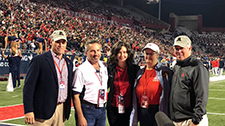 Dr. Clara Curiel recognized at UA Football game with AD Mike Heeke (left) and UA President Robert Robbins (right)Drs.