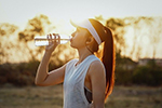 Woman drinks water from bottle to stay hydrated