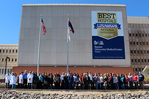 "Clinicians and staff gather to celebrate 2017-18 ""Best Hospital"" rankings in front of old hospital entrance."