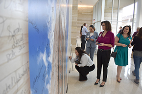 Standing, center: Kim Cota-Robles (in blue) and Kara Balliet (maroon) at the signature wall for new hospital tower