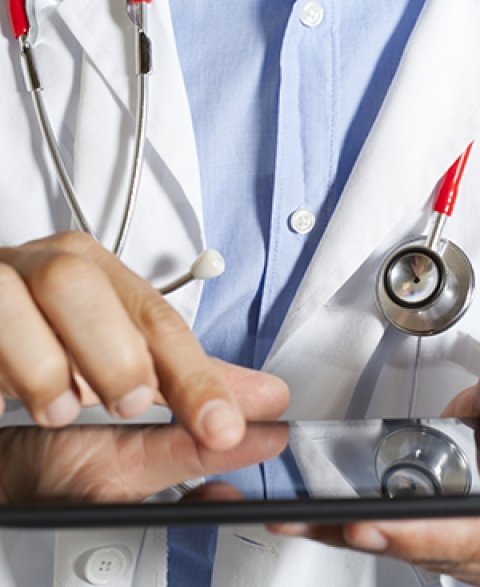 Physician using EHR on electronic tablet