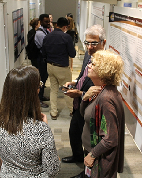 Drs. Christine Laukaitis, Deb Meyers and Sai Parthasarathy confer over a research poster