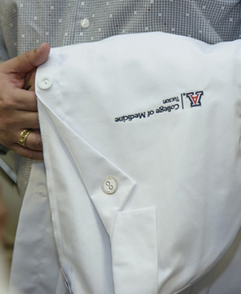 UA College of Medicine Tucson student with white coat over his arm