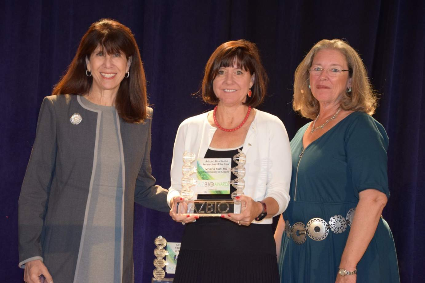 Mara Aspinall, managing director of BlueStone Venture Partners, Dr. Monica Kraft and Joan Koerber-Walker, AZBio president and CEO, as Dr. Kraft is presented with Arizona Biosciences Researcher of the Year honors for 2019